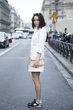 The new street style uniform - a fashion blogger accessories her dress with New Balance trainers during Paris Fashion Week in September 2014.