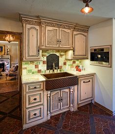 Move upper cabinet above sink to ceiling; add plate rack underneath; way to bring focus to sink that doesn't match rest of cabinetry.