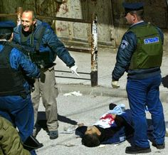 An Israeli policeman stands smiling and pointing next to the body of 16-year-old Sabri Fayez al-Rujoub, who has just been shot dead by an Israeli soldier (Reuters/Nayef Hashlamoun).#FreePalestine Google+