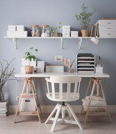 Organisierter Schreibtisch ohne Schubladen in Weiß mit einem Regal darüber, auf dem Boxen, Dosen und Vasen als Aufbewahrung zu sehen sind