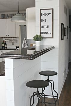 White Shiplap Walls With White Cabinets, Dark Countertops, And Wood Floors!