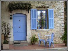 Periwinkle door, window with shutters, and bistro set