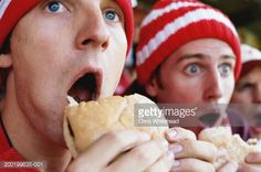 Stock Photo : Football supporters at match, holding hambugers, gasping