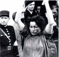 A French woman accused of having consorted with the Germans is driven, with raised hands, to have her hair shorn. Her face carries the marks of her beating by the resistance. This was one of the less edifying aspects of the French fight against the Germans. August 1944.