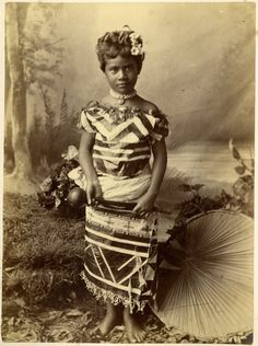 Sa'o tama'ita'i Fa'amu, daughter of Malietoa Laupepa. Photograph (black and white); portrait of Fa'amusami Malietoa wearing a bark cloth dress, a necklace, a flower in her hair, and holding a club, standing in front of a painted backdrop with a plant fibre umbrella beside her.