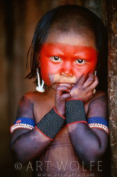 Standing in a doorway this Kayapo toddler has a compelling, intriguing stare for one so young. Like adults, children are painted with purplish black genipapo and red urucu, symbolizing vitality.