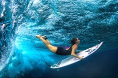 """Surfers """"duck dive"""" under the water to avoid incoming waves so they can get further out to sea."""