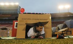 Xander Bowers, a member of Boy Scout troop No. 394 from Garwin, Iowa, comes out from a shelter he made with cardboard boxes during Reggie's Sleepout at Jack Trice Stadium Saturday, March 25, 2017, in Ames, Iowa. Photo by Nirmalendu Majumdar/Ames Tribune http://www.amestrib.com/news/20170325/community-braves-cold-rain-for-youth-homelessness-at-reggie8217s-sleepout