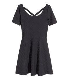 dacebe45fa64 Kortærmet kjole i strukturmønstret jersey. Den er skåret i taljen og har  rundskåret underdel.