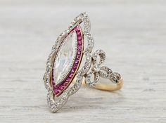 Edwardian ring made in platinum on goldand centered with an approximately .80 caratEGL certified marquisecut diamond with F-G color and SI1 clarity.Accented with calibrecut rubies and single cut diamonds.Circa 1910. USD 14,000