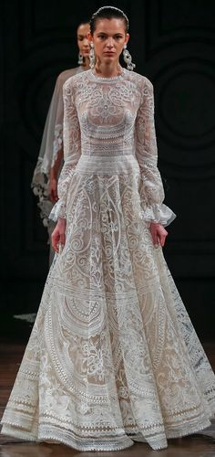 Thread embroidered gown with gathered long sleeves and open back.