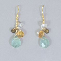 SKU: HY 13831 In a delicate dance of shadow and light, a trio of shimmering beads pirouette around a faceted gemstone in a cluster of sparkling color. Fluorite, citrine and freshwater pearls with Swar