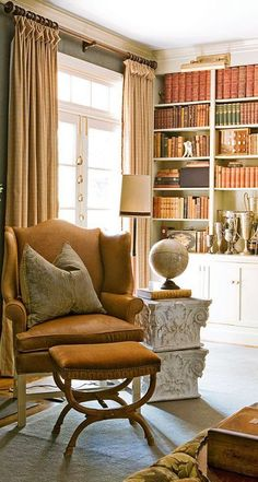 Upholstered walls add a cozy feel to the space; antique books bring an air of history. - Traditional Home ® / Photo: Reid Rolls / Design: Roger Higgins and Ann Shipp