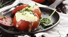 Eggs with mozzarella cheese baked in fresh tomatoes and garnished with chives. Extreme shallow depth of field.