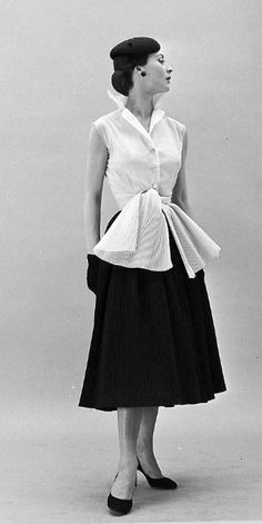 1952 - Gigi is wearing a Givenchy sleeveless blouse with skirt and sash made of tiny accordian pleats, photo by Nat Farbman