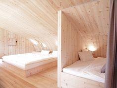 壁で半個室的に2つのエリアに分けられた、暖かみのある板張りのベッドルーム