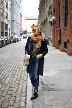 Laurie Ferraro is wearing an authentically seasonal outfit here, pairing a beige scarf with a longline blazer and a pair of patent Chelsea boots. Wear this look with jeans and in autumnal hues to get that classic fall style. sweater/Jeans: Citizens of Humanity, Blazer: Oak & Fort, Boots: Zara.