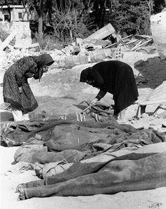 Sabra and Shatila massacre of Sept.1982 - Two Palestinian woman, holding their noses against the smell of death, lift blankets off corpses as they search for family members killed by Christian militiamen.  Pic by Bill Foley of Associated Press