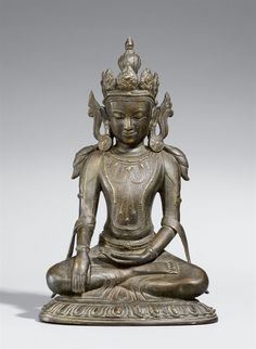 An Arakan bronze figure of a bejewelled Buddha Shakyamuni. 15th/16th century  An Arakan bronze figure of a bejewelled Buddha Shakyamuni seated in meditation (padmasana) on a flat lotus, the right hand in bhumisparsha mudra, the left hand in dhyana mudra above the feet, an intricate foliate crown on the head, large disc-shaped earings and multiple necklaces on the bare chest. 15th/16th century.  Height 32 cm