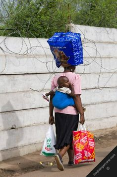south africa transport woman carrying child on-her back heavy load head and-her arms vertical. THIS IS MULTITASKING!!!!