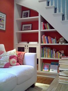 Shelves under stairs - I love the bright wall colour through the white shelves