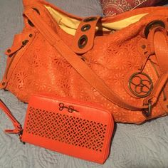Orange Jessica Simpson wristlet and large purse This is a matching large Jessica Simpson purse and matching wristlet. I've carried the purse and I love it it has pockets everywhere!! And it has double straps and it has a few ink pen marks inside and the wallet has never been used. This is a great purse to have you can carry everything in this purse I'm tellin you it's awesome lol!! Please give it a look thanks a lot! Jessica Simpson Accessories Sunglasses