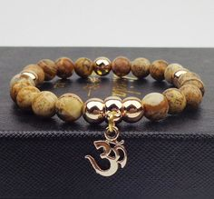 This beautiful bracelet is made with Natural Stone and features an Om Gold Plated Charm framed by Golden Beads. This charm represents the Sacred Sound of Meditation in eastern traditions. This bracele