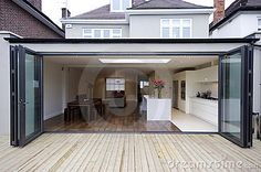 House extension open bifold doors into garden wooden decking