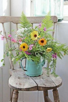 Flowers in blue metal pitcher on wooden chair