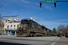 Norfolk Southern comes through the intersection of and Broad in Augusta, Georgia. The railroad runs right down the middle of the street fter crossing the Savanah River out of South Carolina. Southern Trains, Dazzle Camouflage, Augusta Georgia, Southern Railways, Railroad Photography, Norfolk Southern, Double Take, The World's Greatest, Unique Art