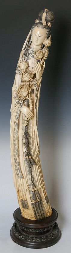 """LARGE 19TH C. CHINESE CARVED IVORY BEAUTY Chinese carved ivory Empress or Beauty, 19th C., holding flowers in hand, wearing long flowing gown, monochrome, with wooden stand. Weight: 10.5kg Size: 42"""""""