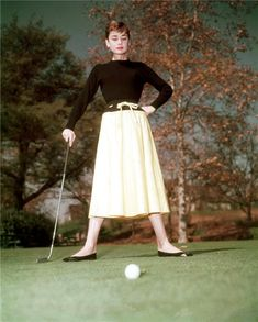 Full-length view of Belgian-born actor Audrey Hepburn - standing on a golf course, holding her putter, with a golf ball on the green in the foreground. She wears a black top and a yellow drawstring skirt. (Photo by Hulton Archive/Getty Images) Style Audrey Hepburn, Audrey Hepburn Photos, Golfer, Vintage Golf, Influencer, Hollywood Icons, Top Celebrities, Golf Fashion, Women's Fashion