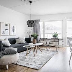 Biało-szary salon wiele zyskał dzięki oryginalnemu oświetleniu. Ciemna lampa o geometrycznym kształcie zdobi wnętrze i idealnie komponuje się z grafitową sofą.