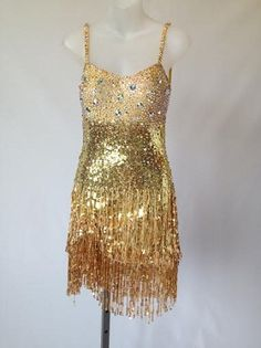 "Fun and vibrant , this gold sequined dress is a sexy little number on the floor! Covered with Swarovski stones. Has Bra cups and body suit. Fits sizes 2-6 and best for heights above 5'2"" and comes with one matching cuff bracelet. Designed by DSI London"