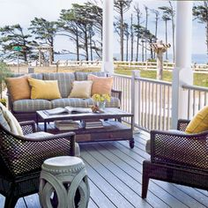 This porch is classic coastal with plaid fabric and rattan furniture. For more porches and patios, visit www.coastalliving.com