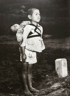 Japan, Nagasaki, 1945.  In the photo, the boy stands erect, having done his duty by bringing his dead brother to a cremation ground. Standing at attention was an obvious military influence. Looking at the boy who carries his younger sibling on his back, keeps a stiff upper lip, tries so hard to be brave is heart-breaking. He has epitomized the spirit of a defeated nation.