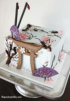 This asian-adorned cake was made for a stylist. It features cherry blossoms, fans, butterflies, chop sticks, and a pagoda.