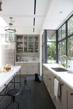 Grey-green cabinets, black metal framed windows, industrial accessories