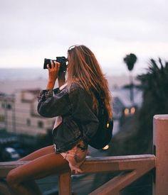 Chica viendo la ciudad a través de unos vinoculares
