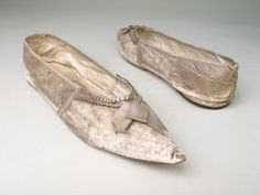 Manchester City Galleries item 1947.934    Made in Bath by Abraham Moore    1800-15 Grey leather spotted in close diamond pattern in white, bound in grey silk ribbon over linen and kid.    Elongated and pointed toes. Low round fronts edged with pleated grey silk ribbon and trimmed with bow. Wedge heel.