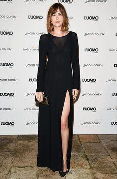 Dakota Johnson wears a black long-sleeve gown with a thigh-high slit, black pumps, and a metallic clutch