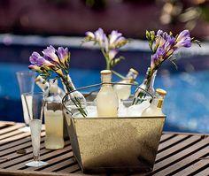 O balde de gelo fica muito mais charmoso quando algumas das garrafas de refrigerante são preenchidas com flores.