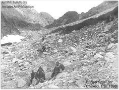 Klondike Gold Rush prospectors and Alaska Native packers rest while others make their way up the rocky path toward The Scales on their way to the Chilkoot Pass summit in 1897.  A sturdy people, the Chilkat Indian men could pack up to 200 pounds on their backs and women and children could carry about 75 pounds each. They charged the stampeders $1 per pound to haul their gear up the trail.