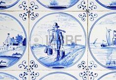 Dit is een delftsblauwe tegel met daarin een man die loopt met tonnen aan zijn schouders.