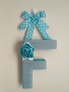 Yarn wrapped letter, decorated with coordinating ribbon and flowers Facebook: PartywithStaci