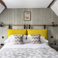 Grey & white bedroom with wood panelling in Small Space Design Ideas. Small white & grey attic bedroom with wood panelling, DIY headboard and yellow accents.