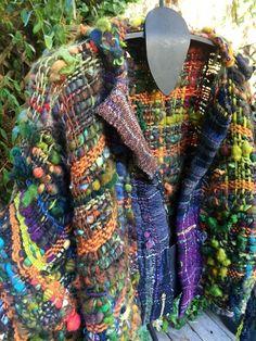 Una tejida a mano lana artesanal y mano hizo girar el chaqueta. Lleno de vida, texturas y colores, muchos hilos de arte.. .no siempre reproducibles. Bandas delanteras de Saori tejidas a mano y detalle de franja larga convertible cuello espalda. Esta pieza es realmente muy ligera y libremente tejido de paño. Voltear cada mitad de la franja de collar único alrededor al frente para un detalle de efecto bufanda si usted elige. Volver los puños de manga largas. Alrededor del 85% de esta pieza es…