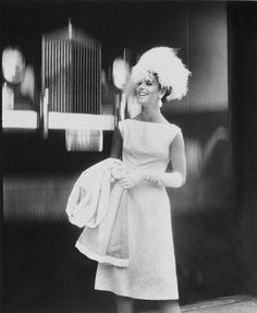 Model is wearing a white brocade dress by Nat Kaplan, long white gloves, and an ostrich cloche by Miss Alice, with a coat draped over her arm.