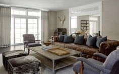 Modern country living room features a long brown chesterfield sofa adorned with dark grey pillows ...