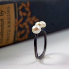 A delicate square band holds three beautiful AAA freshwater pearls almost hovering above it. The band has been oxidized to make a beautiful contrast with the white purity of the pearls.    This ring is ready to ship in a size 7, if you want another size please give me a week to make it and ship it.    NOTE ON DURABILITY: This ring is very durable, I have one and I wear it A LOT. Pearls by nature are delicate, so it is recommended to take it off if you are doing dishes or any housework. The…